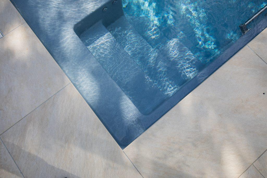 Betongrau-blaue Poolfarbe mit Glitzerpigmenten verstärken den Eindruck von tiefblauem Meerwasser.